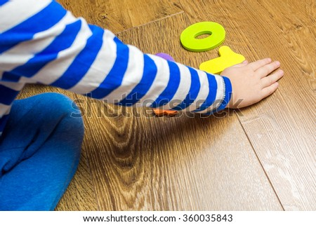 young boy demonstrating his collection of numbers while sitting on brown wooden floor - stock photo