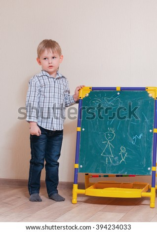 young boy draws with chalk on the blackboard - stock photo