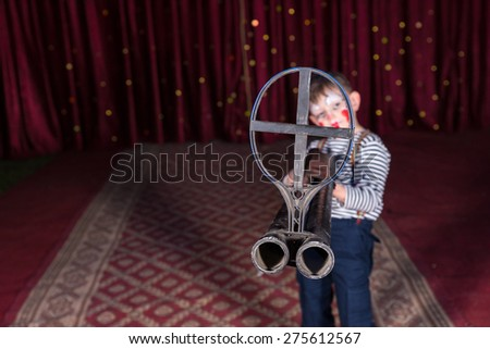 Young Boy Dressed as Clown Aiming Large Double Barreled Gun with Iron Sight at Camera and Standing on Stage - stock photo