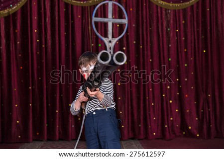 Young Boy Dressed as Clown Holding Large Gun with Iron Sight at End of Barrel, Standing on Stage with Red Curtain - stock photo