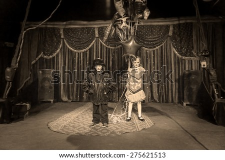 Young Boy Dressed as Clown Wearing Leather Jacket and Helmet Standing on Stage with Girl in Bright Costume Holding Strings of Foil Balloons, Monochrome Image Gives Old Time Feel - stock photo