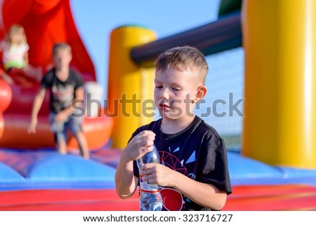 Young boy drinking bottled water as he stands in front of a colorful plastic jumping castle at a playground or fairground - stock photo
