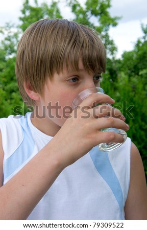 Young boy drinks water out of cups  after sports - stock photo