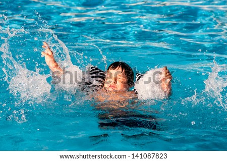 Young boy drowning in the pool - stock photo