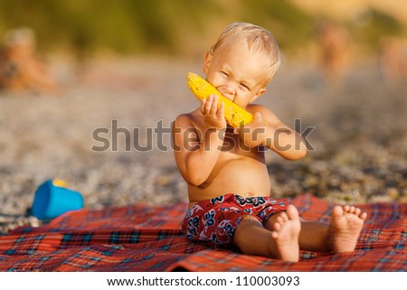 Young boy eating an ear of grilled corn on the cob - stock photo