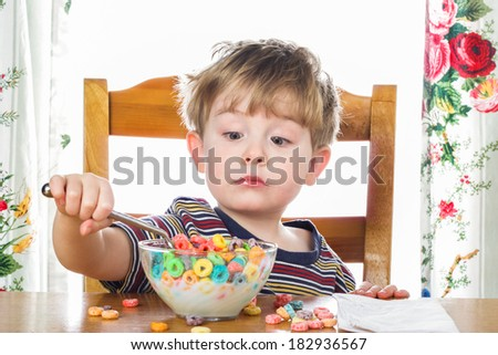Young boy eating breakfast cereal - stock photo