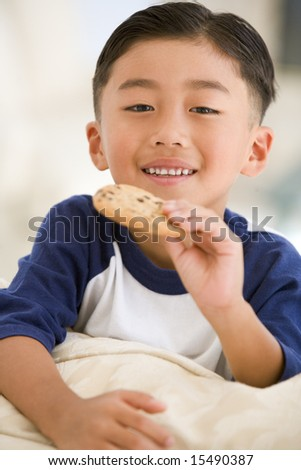 Young boy eating cookie in living room smiling - stock photo