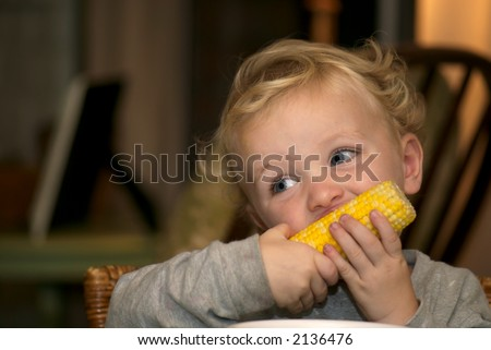 Young boy eating corn for dinner - stock photo