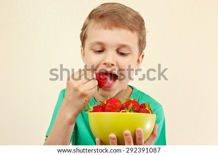 Young boy eating fresh strawberries from a bowl - stock photo