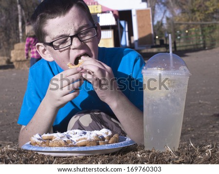 Young boy eating funnel cake. - stock photo