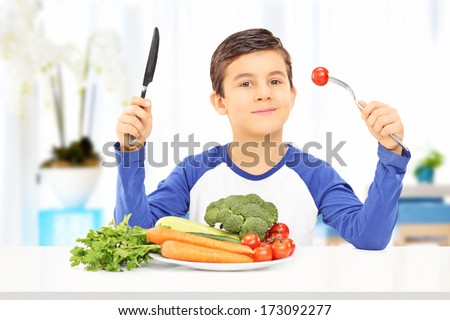 Young boy eating healthy meal seated at a table - stock photo