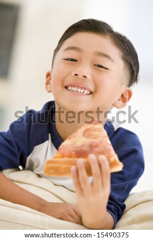 Young boy eating pizza slice in living room smiling - stock photo