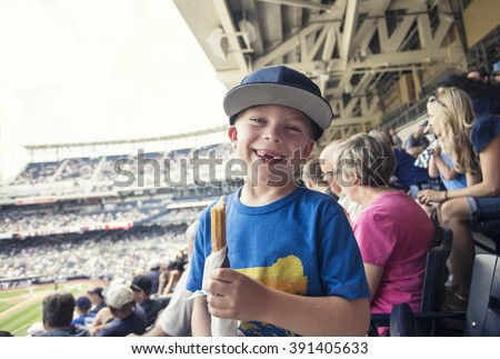 Young boy enjoying a day watching a professional baseball game - stock photo