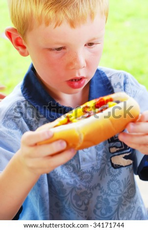 Young boy excited to eat a big hot dog - stock photo