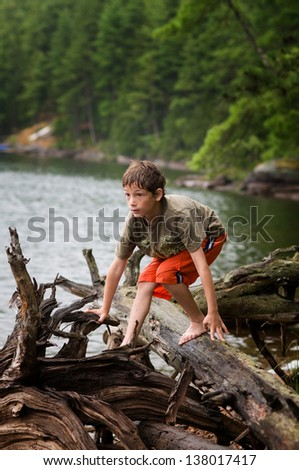 young boy exploring by a remote lake - stock photo
