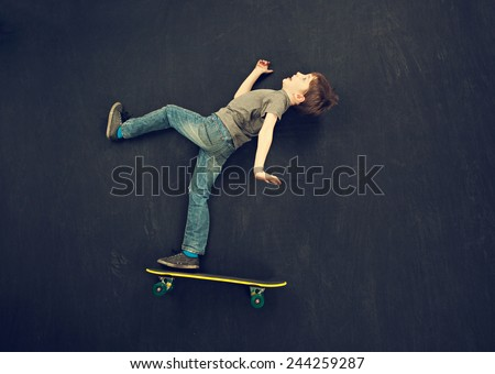Young boy falling off a skateboard - stock photo