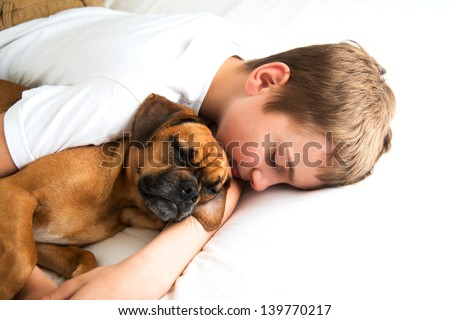 Young Boy Fell asleep Hugging his Dog - stock photo