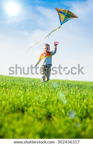 Young boy flies his kite in an open field. Little kid playing with kite on green meadow. Childhood concept. - stock photo
