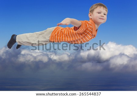 Young boy flying with cloud sky in background - stock photo