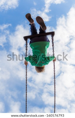 Young boy free as a bird on a swing against a blue sky with white puffy clouds - stock photo