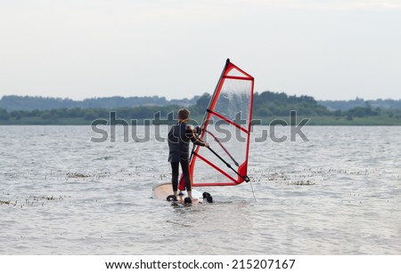 Young boy getting windsurfing lessons along a mild shoreline - stock photo