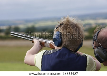 Young boy given advice on  clay pigeon shooting - stock photo