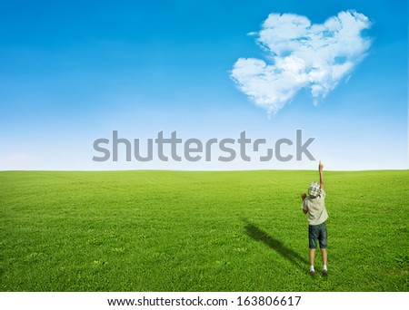young boy green grass field pointing blue sky with clouds in shape of heart - love concept - stock photo