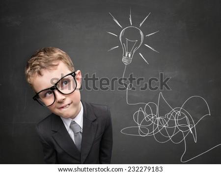 Young boy having an idea. Light bulb above his head - stock photo