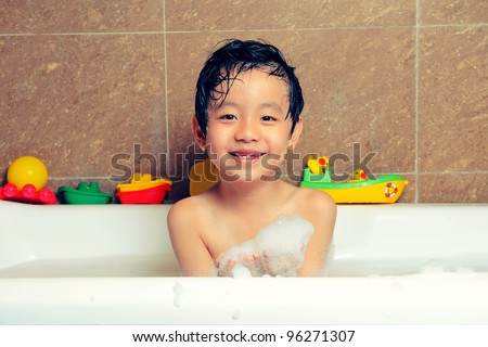 Young boy having bubble bath with toys - stock photo