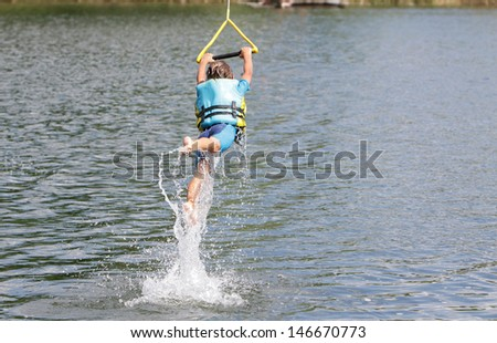young boy having fun in water, wake boarding - stock photo