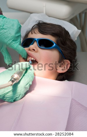 Young boy having his teeth polished at the dentist, after dental cleaning - stock photo