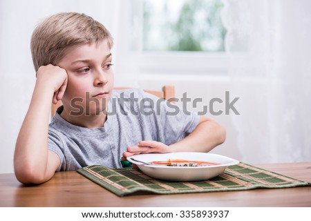 Young boy having no appetite for dinner - stock photo