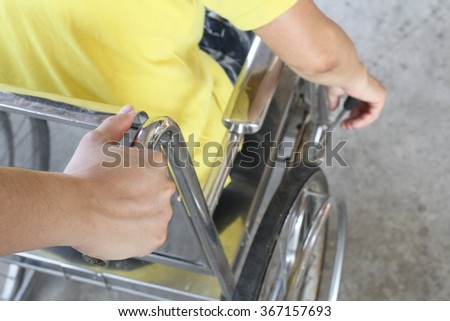 Young boy helping his mother on wheelchair walking in the park - stock photo