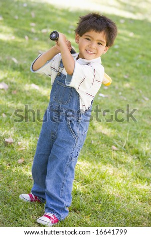Young boy holding baseball bat outdoors smiling - stock photo