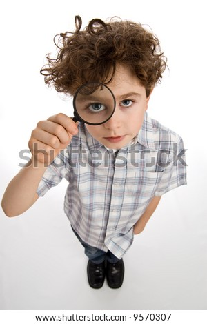 Young boy holding magnifying glass - stock photo