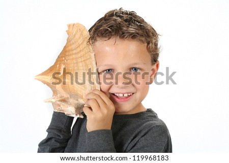 Young boy holding sea shell up and listening to the sounds of the ocean - stock photo