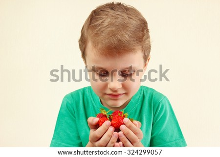Young boy holds a handful of fresh ripe strawberries - stock photo