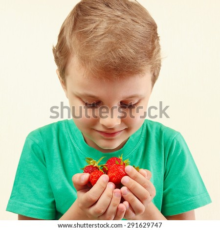 Young boy holds a handful of fresh strawberries - stock photo