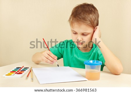 Young boy in a green shirt going to paint watercolors - stock photo