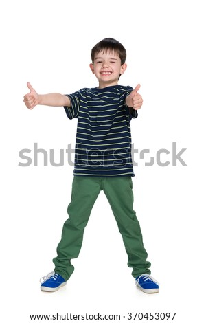 Young boy in a green trousers holds his thumbs up on the white background - stock photo