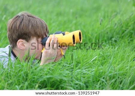 Young boy in a meadow looking through binoculars - stock photo