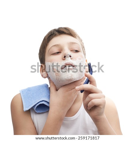 Young boy in a sleeveless white shirt with his face covered with the shaving foam, in process of shaving, composition isolated over the white background - stock photo