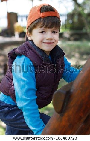 Young boy in cap climb up on ladder, smile - stock photo