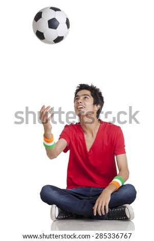Young boy in casual wear tossing soccer ball while sitting cross-legged over white background - stock photo