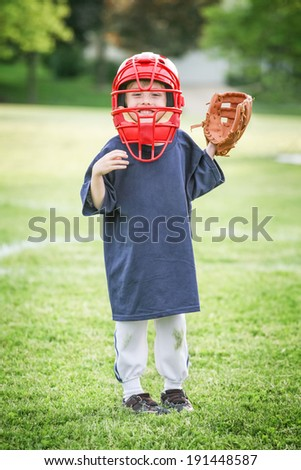 Young boy in Catchers mask and glove - stock photo
