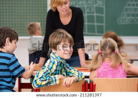 Young boy in class turning in his chair to smile at the camera as a female teacher chats to the other young students in the background - stock photo