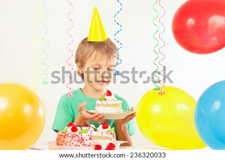 Young boy in festive hat with a piece of birthday cake - stock photo
