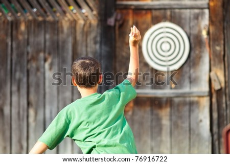 Young boy in green t-shirt playing darts outdoor - stock photo