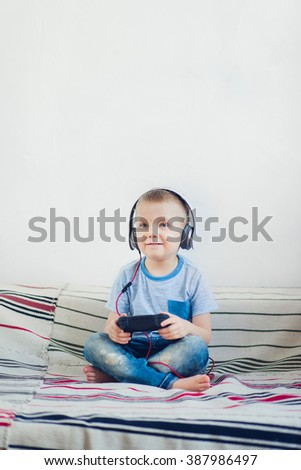 Young boy in headphone enjoys playing games - stock photo