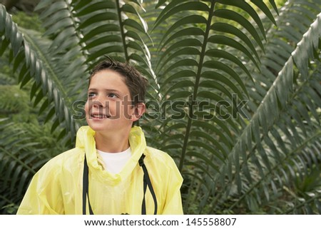 Young boy in raincoat standing in front of large fern during field trip - stock photo